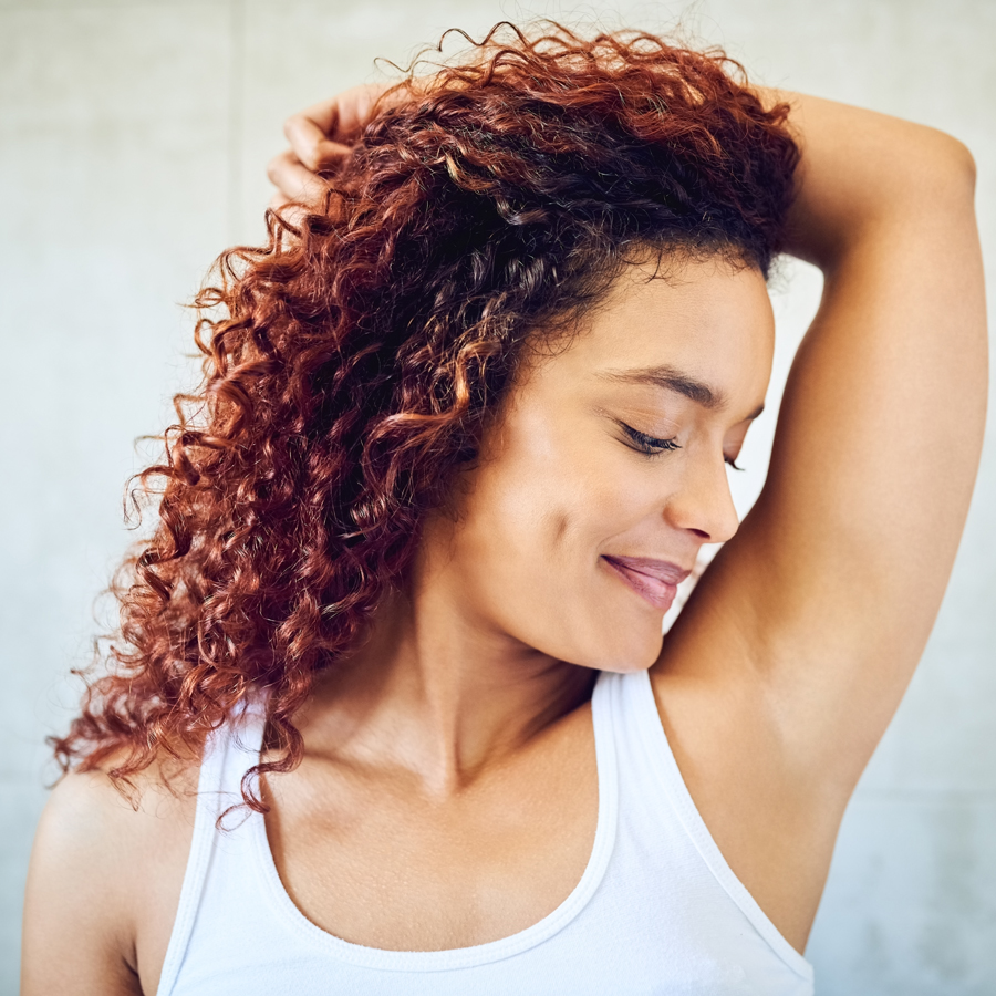 Happy woman sniffing armpit